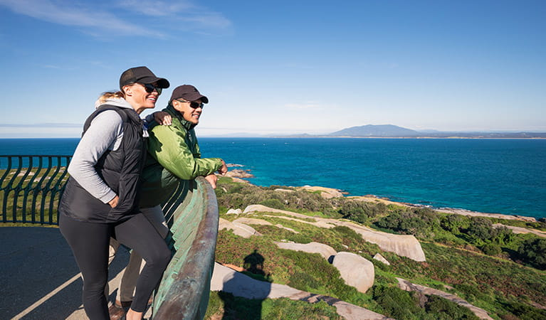 A woman and man lean on the balcony atop Montague Island Lighthouse. Photo: Daniel Tran/OEH