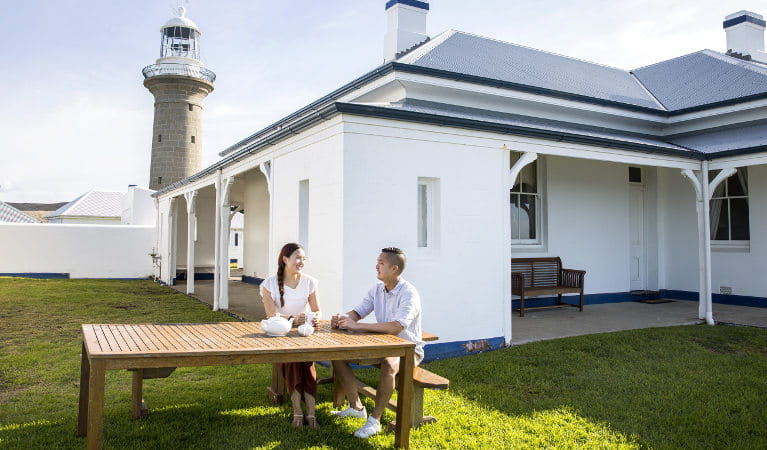 A couple sits at the outdoor wooden table beside the Montague Island Head Lighthouse Keeper's Cottage. Photo: Tim Clark/DNSW