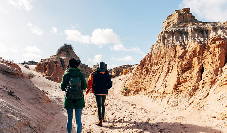 2 girls walk past sand-sculpted formations, Walls of China, Mungo National Park. Photo: Melissa Findley/OEH