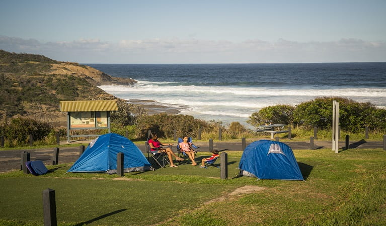 Family sitting beside their tents at Frazer campground, Munmorah State Conservation Area. Photo: John Spencer/OEH