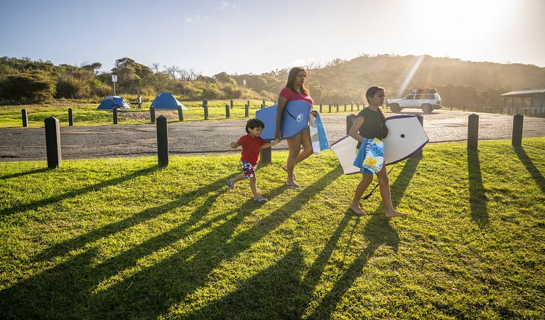 Family walking to Frazer beach with their swimming gear at Frazer campground, Munmorah State Conservation Area. Photo: John Spencer/OEH