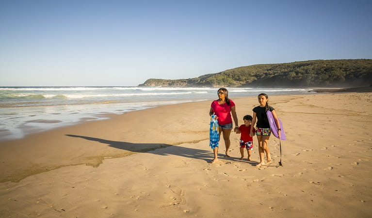 Family walking along Frazer beach, Munmorah State Conservation Area. Photo: John Spencer/OEH