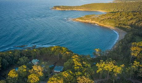 Aerial view of Judges House (right), neighbouring Yellow Rock Beach House and the coastline, Murramarang National Park. Photo: John Spencer ©DPIE