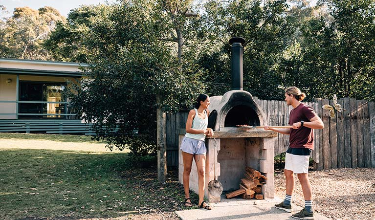 A couple use the pizza oven at Depot Beach campground, Murramarang National Park. Photo: Melissa Findley/OEH.