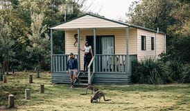 A couple at Pretty Beach cabins, Murramarang National Park. Photo: Melissa Findley/OEH.