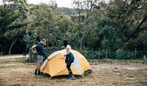 A couple outside their tent at Pretty Beach campground, Murramarang National Park. Photo: Melissa Findley/OEH.