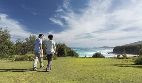 Couple walking at Pretty Beach picnic area in Murramarang National Park. Photo credit: David Finnegan. ©DPIE