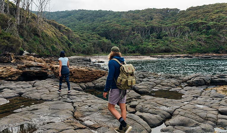 A couple on a rock platform, low tide, Pretty Beach to Snake Bay walk, Murramarang National Park. Photo: Melissa Findley/OEH.