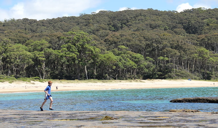 Child exploring the rock platform near Depot Beach. Photo: John Yurasek/DPIE