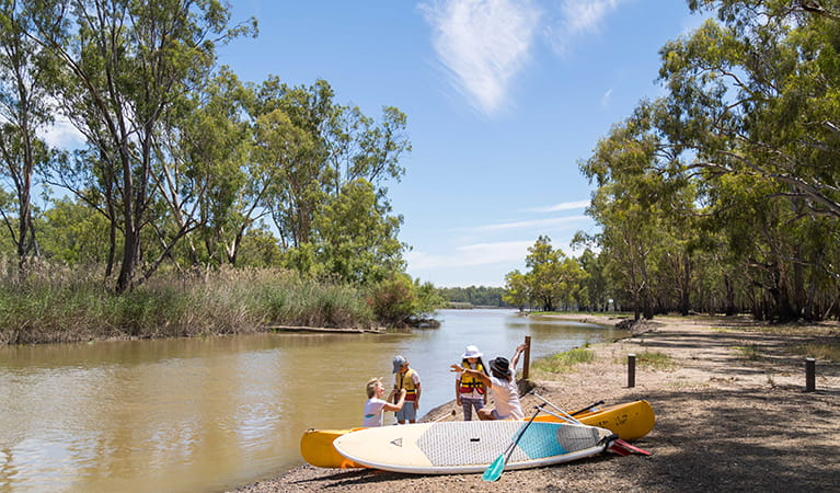 Family with lifejackets, paddle boards, canoe and paddles at Barmah Lakes day visitor area. Photo: B Ferguson/OEH