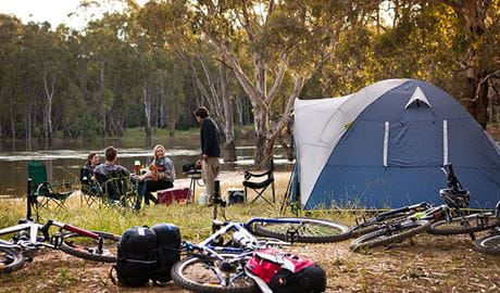 A group of friends next to their tent, with their bikes in the foreground on the banks of the river at Murray Valley campgrounds. Photo: David Finnegan © DPIE