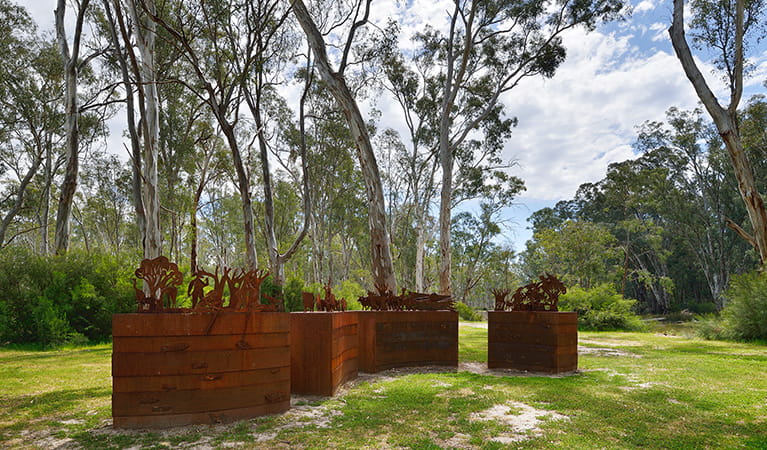 Wide view of sculpture set on grassy flat amongst river red gums in Murray Valley Regional Park. Photo: Gavin Hansford/DPIE