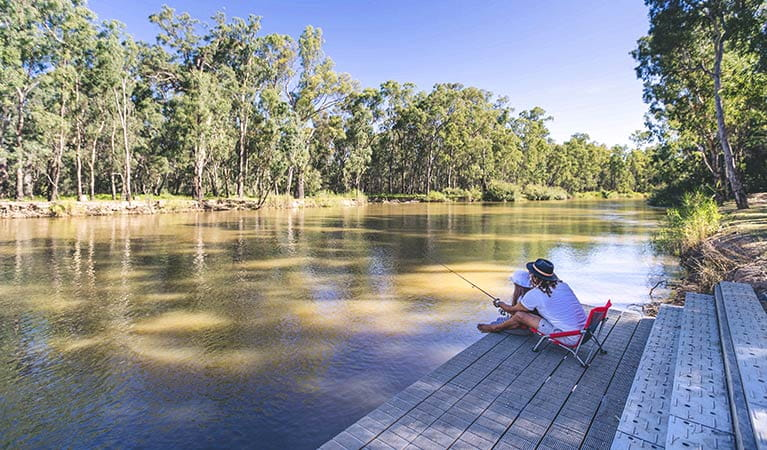 Father and daughter fishing from a deck, Swifts Creek campground, Murray River National Park. Photo: B Ferguson/OEH