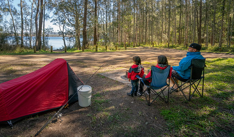 Family watching the lake by their tent at Bungarie Bay campground. Photo: John Spencer/OEH