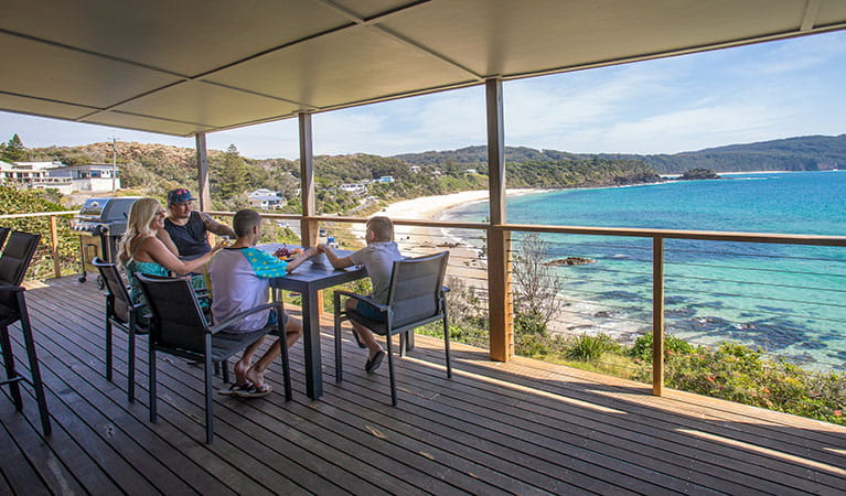A family on the deck of Davies Cottage with Boat Beach and Sugarloaf Bay in the background. Photo: John Spencer © DPIE