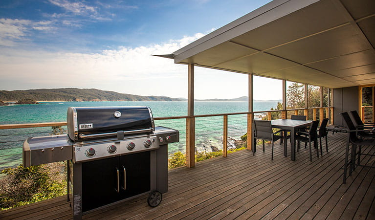 A gas barbecue and outdoor seating on the deck of Davies Cottage, with Sugarloaf Bay in the background. Photo: John Spencer © DPIE