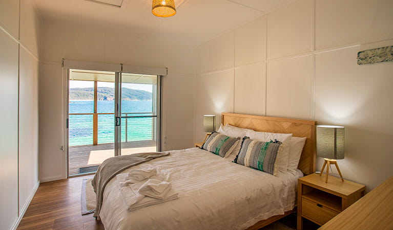 A bedroom with queen bed and ocean views in Davies Cottage. Photo: John Spencer © DPIE
