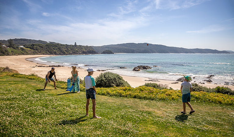 A family playing cricket on the grass below the cottage with Boat Beach in the background. Photo: John Spencer © DPIE