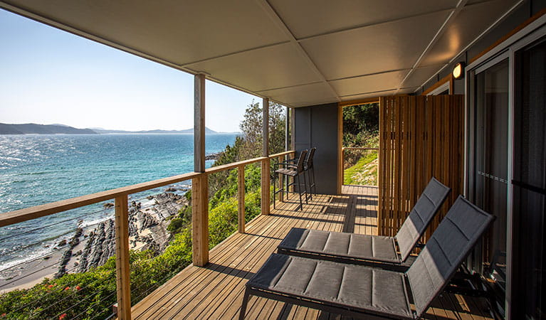 Sun lounges on the balcony of Davies Cottage overlooking Boat Beach and Sugarloaf Bay. Photo: John Spencer © DPIE