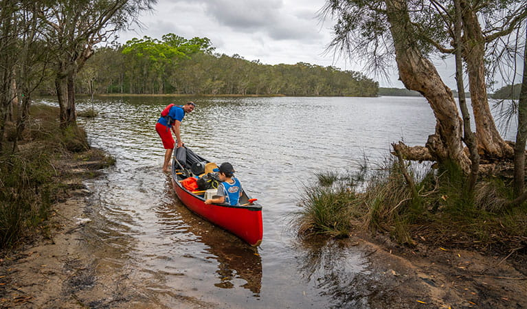 2 people in a canoe on Boolambayte Lake at Violet Hill campground in Myall Lakes National Park. Photo: John Spencer © DPIE