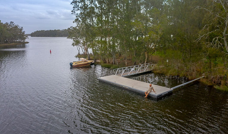 A man sitting on the wharf at Violet Hill campground in Myall Lakes National Park. Photo; John Spencer © DPIE