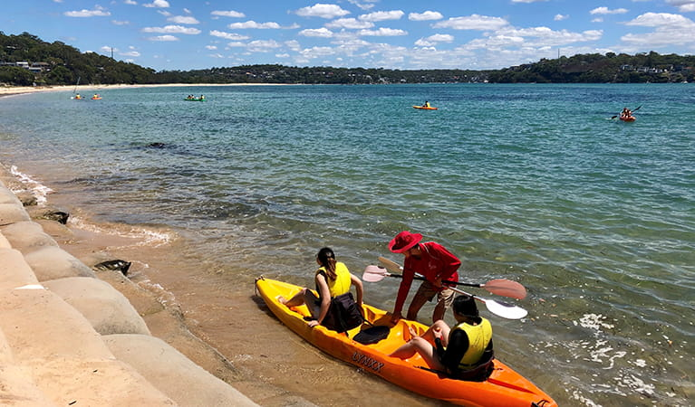 People being helped into a kayak in ocean, at Bonnie Vale picnic area. Photo: OEH/Natasha Webb