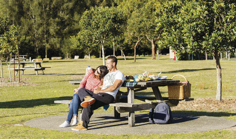 A couple enjoying the view from a picnic table at Bonnie Vale picnic area in Royal National Park. Photo: Simone Cottrell/OEH
