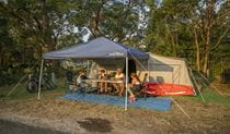 Family enjoying a drink by their tent at Bonnie Vale campground. Photo: John Spencer/OEH