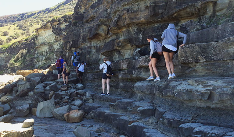 People walking along steep rock face to Figure Eight Pools. Photo: Claire Competiello/OEH