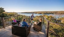 A family enjoying the view from the balcony of Hilltop Cottage in Royal National Park. Photo: John Spencer © DPIE