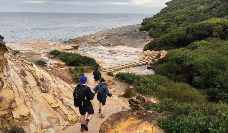 Walkers descending an ochre-coloured sandstone slope before crossing a creek using large stepping stones, with views out over the ocean. Credit: Natasha Webb. © Natasha Webb/DPIE
