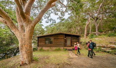 Four people walk towards Weemalah Cottage in Royal National Park. Photo: John Spencer/OEH