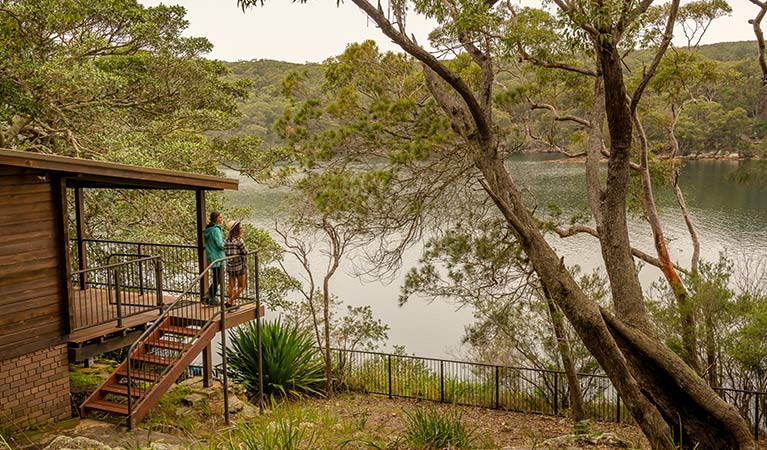 A couple stand on the balcony of Weemalah Cottage, Royal National Park. Photo: John Spencer/OEH