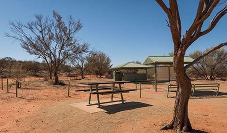 A picnic table, information sign and barbecue shelter at Olive Downs campground in Sturt National Park. Photo: John Spencer/DPIE