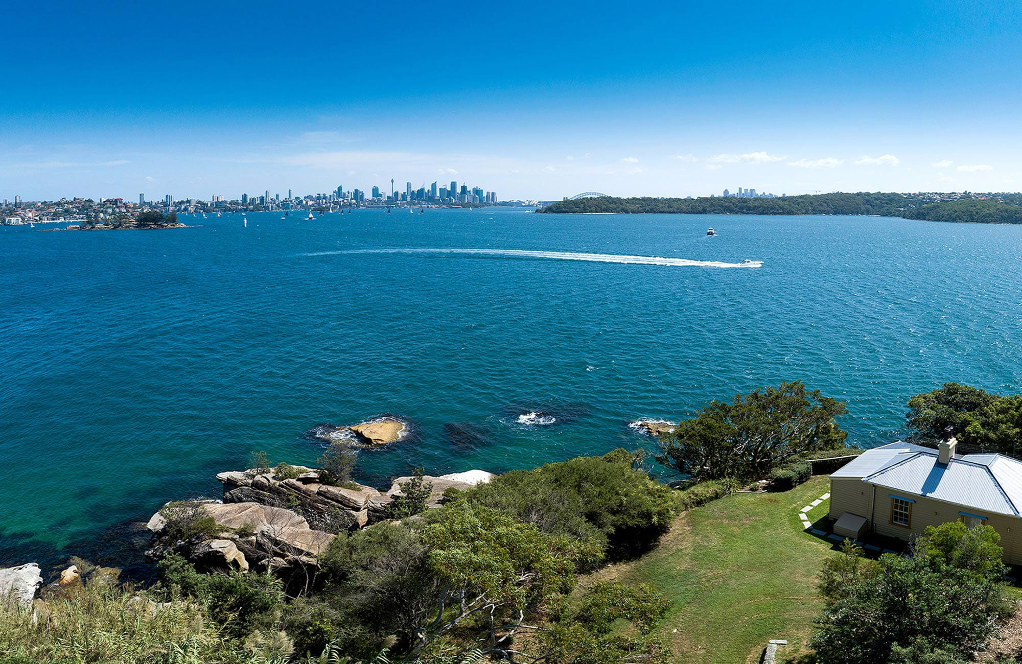 Aerial view of Steele Point Cottage in Sydney Harbour National Park, with city skyline in the distance. Photo: G Pickford/OEH.