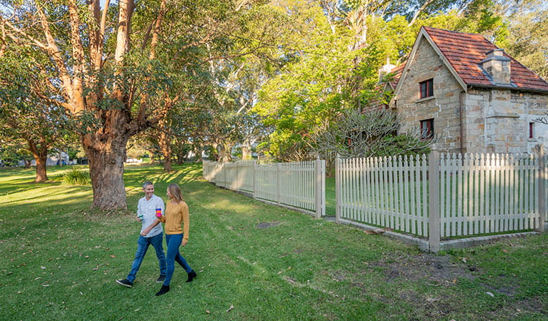 A couple walking out the front gate of Gardeners Cottage in Sydney Harbour National Park. Photo: John Spencer/DPIE
