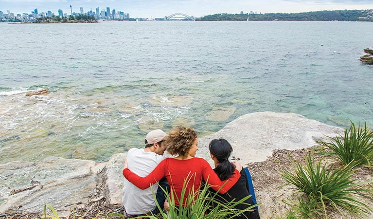 Friends admiring the view of the Sydney Harbour skyline from Hermitage Foreshore track. Photo: Simone Cottrell/DPIE