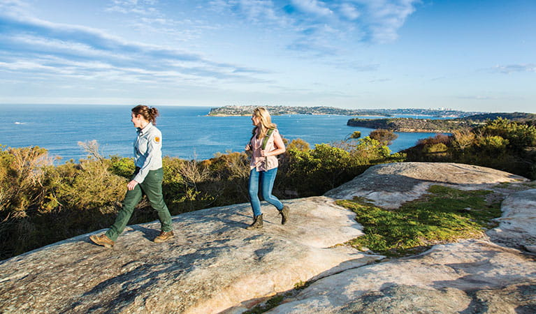 A field officer and park visitor walking along the rocks on Manly scenic walkway with a view of Middle Head in the background in Sydney Harbour National Park. Photo: Simone Cottrell/DPIE