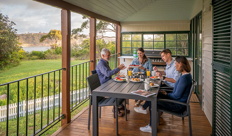 A group of friends having breakfast on the verandah at Middle Head Officers Quarters, Sydney Harbour National Park. Photo: John Spencer/DPIE