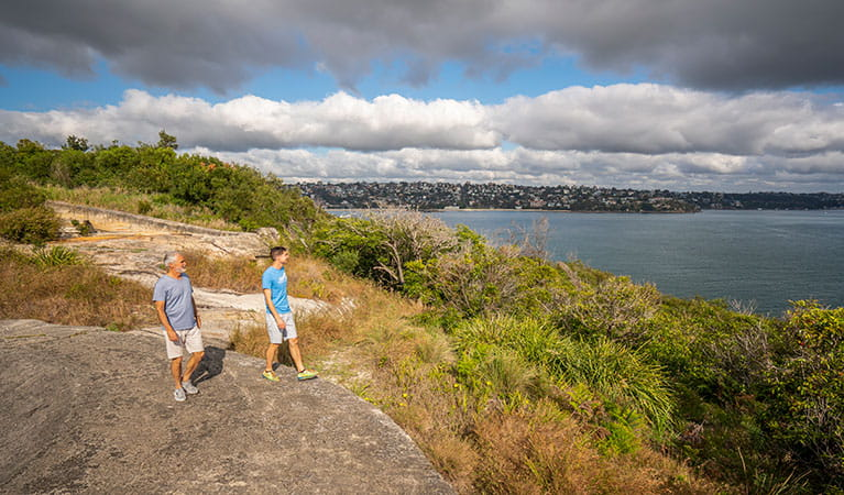 Two people looking out over the harbour at Middle Head forts in Sydney Harbour National Park. Photo: John Spencer/DPIE