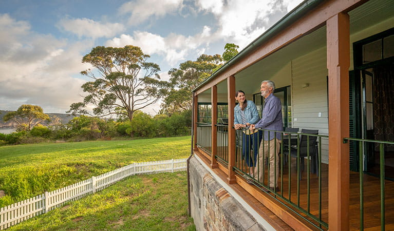 Two people standing on the back verandah of Middle Head Officers Quarters in Sydney Harbour National Park. Photo: John Spencer/DPIE