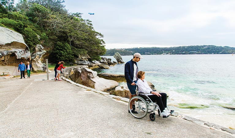 Wheelchair user admiring views of Shark Beach from the wheelchair accessible path in Nielsen Park. Photo: Simone Cottrell/DPIE