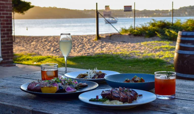 Food and drinks on a table with Sydney Harbour in the background. Photo: Q Station
