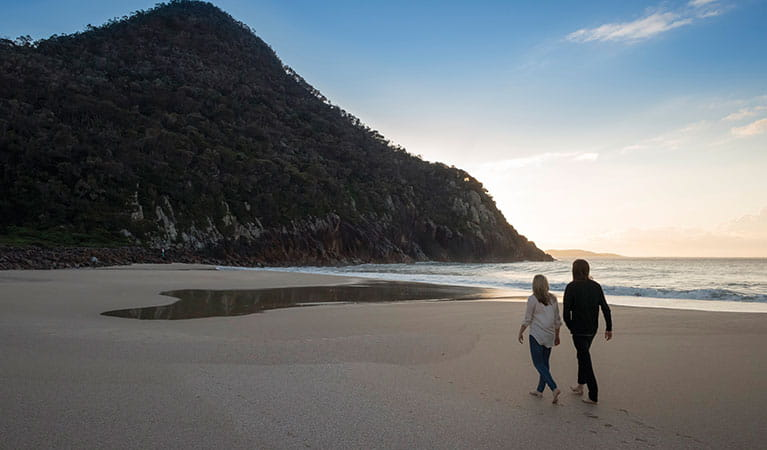 Couple walking on Zenith beach in Tomaree National Park. Photo: OEH/J Spencer