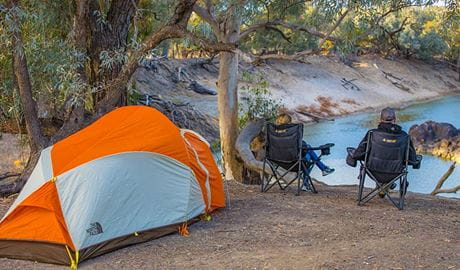 Campers sit next to a tent overlooking the river, Darling River campground, Toorale National Park. Photo: Joshua Smith/OEH.