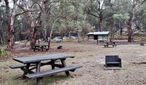 Picnic tables, wood barbecues and picnic shelter on a grassy area surrounded by bushland.  Photo: Shari May/DPIE