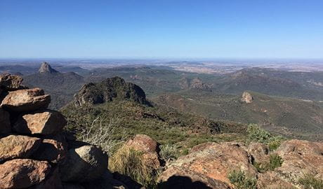 View past a rocky ledge to distant peaks, domes and plains at Bluff Mountain lookout in Warrumbungle National Park. Photo: May Fleming © May Fleming