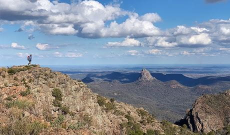 A hiker on Bluff Mountain's summit with mountainous landscape in the distance. Photo: Eveline Chan/OEH