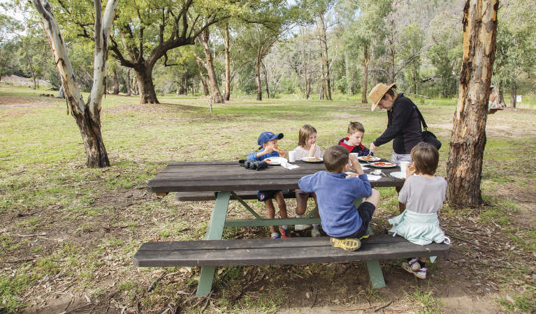 An adult and group of kids having lunch at a picnic table in Warrumbungle National Park. Photo: Simone Cottrell/RBG