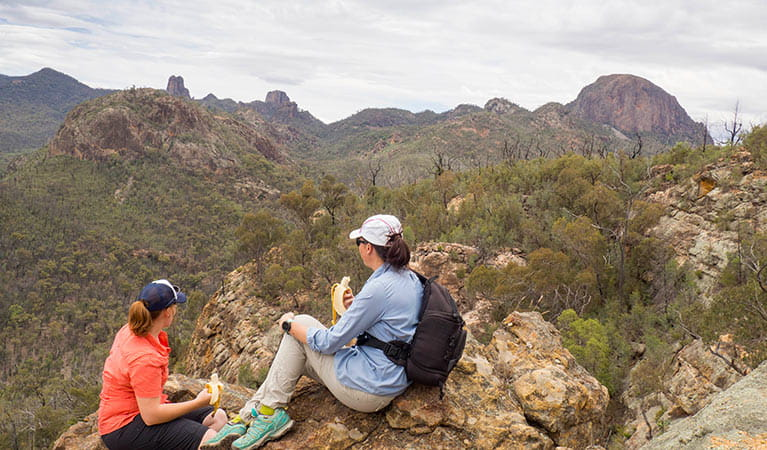2 bushwalkers have a snack on Fans Horizon walking track in Warrumbungle National Park. Photo: Leah Pippos/OEH.